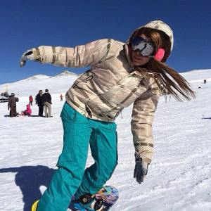 Young woman snowboarding in Tochal, Iran