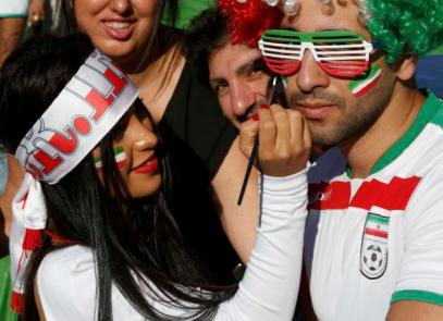 An Iran supporter applies face paint to another fan before the Asian Cup Group C soccer match betweeen Iran and Bahrain at the Rectangular stadium in Melbourne