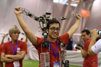 AUT-UofM team member celebrating with his robot. Photo credit: ilpost.it via STR/AFP/Getty Images