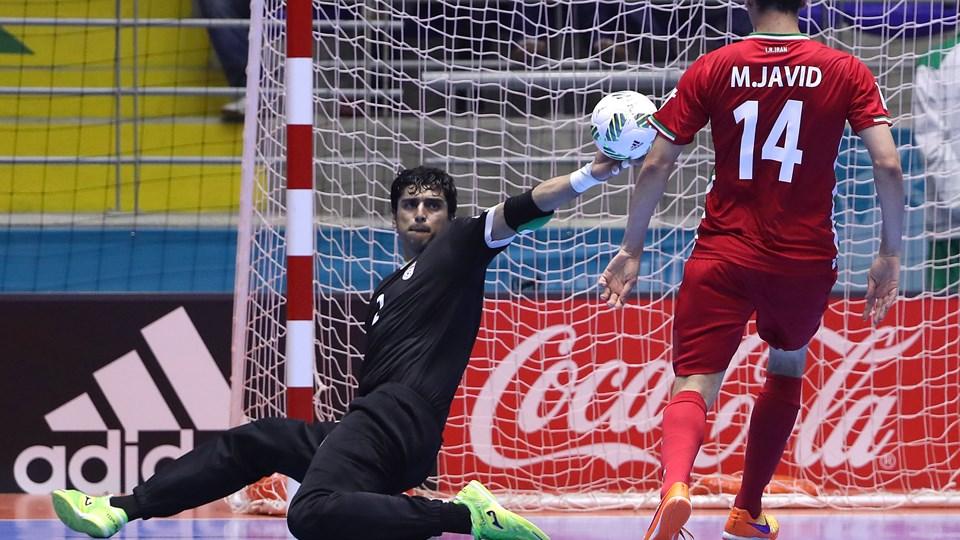 Goalkeeper Alireza Samimi of Iran gets a hand on the ball ...
